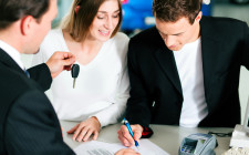 Couple signing sales contract at car dealer