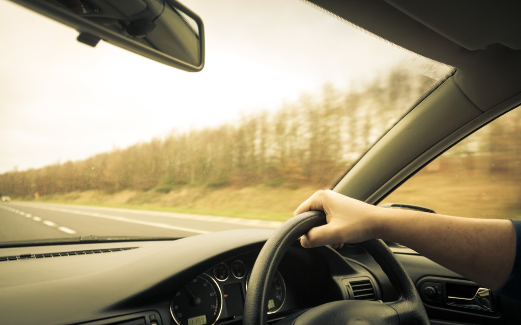Male driver hands holding steering wheel of a car and road