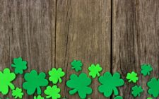 paper shamrock cutouts on wood table